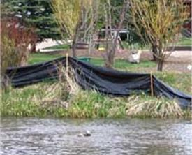 body of water with black tarp to contain runoff