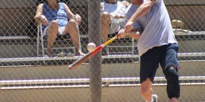 A man swinging at a softball.